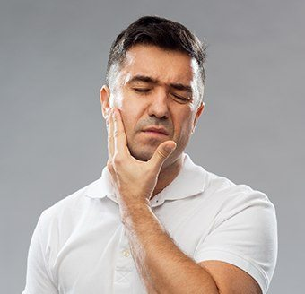 Man in pain holding jaw