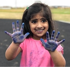 Little girl holding up hands with blue paint